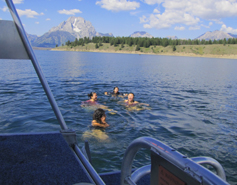 in the foreground, the deck of a boat, in the middle girls treading water and calling out, in the background Mount Moran