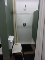 shower with a small seat just outside it for a bag