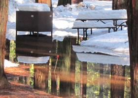 bear box and picnic table with snow on top, water below