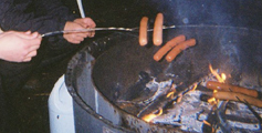 hot dogs on sticks over a campfire