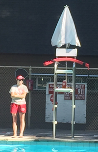 lifeguard standing at a pool deck, with her rescue tube up the the lifeguard stand, instead of on her person