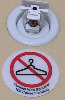 sprinkler head and sign with a drawing of a clothes hanger saying that if you hang anything from the sprinkler head it will cause flooding