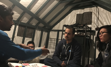 four people in a tent cabin playing cards