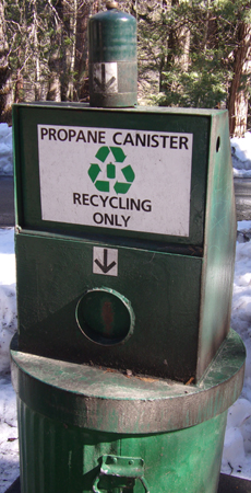 a trash can with a sign that says propane canister recycling only