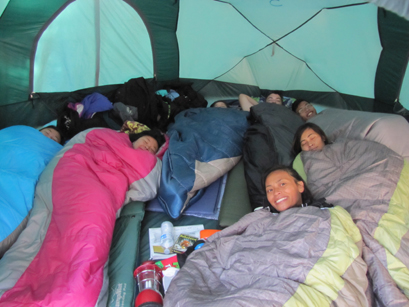 seven people in sleeping bags in an eight person tent