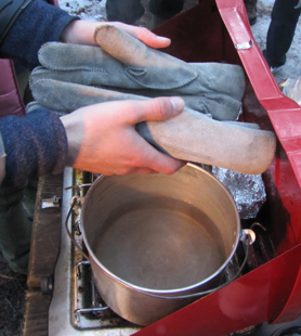 holding a pair of gloves over a camp stove with a pan of water below