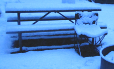 snow covered picnic table and pop-up chair