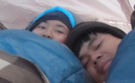 girl and guy in knit hats in their sleeping bags