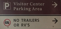 sign that says Visitor Center parking area, no trailers or RVs
