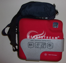 a e d in a soft case in a metal bracket on a wall, with a fanny pack with more equipment above it
