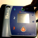 gloved finger poised over AED on off button