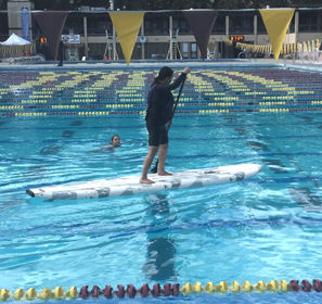 woman in a lifejacket on a stand-up paddleboard at a swimming pool