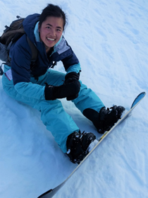 girl on a snowboard sitting in the snow