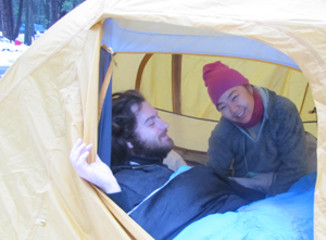 Guy and girl in tent with snow in background