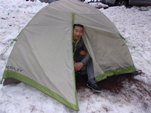 guy sitting at door way of in tent with lots of snow on the ground all around
