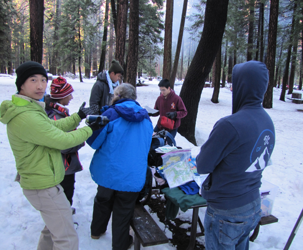 group of people around a picnic table in the snow looking at maps