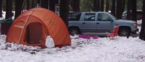 orange tent with snowman and Chevy Suburban