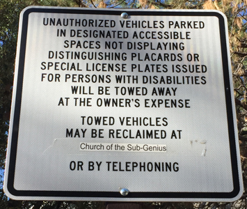 sign that says towed vehicles may be reclaimed at Church of the sub-genius