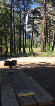 picnic table and grill, view of Yosemite Falls in background partially obstructed by trees