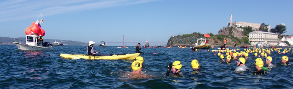 a few swimmers, kayakers and a trawler with red buoys