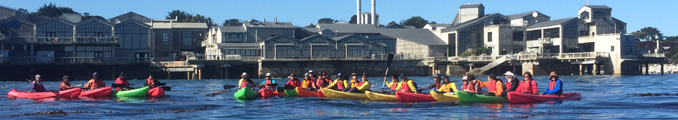 line of kayaks with Monterey Bay Aquarium behind them