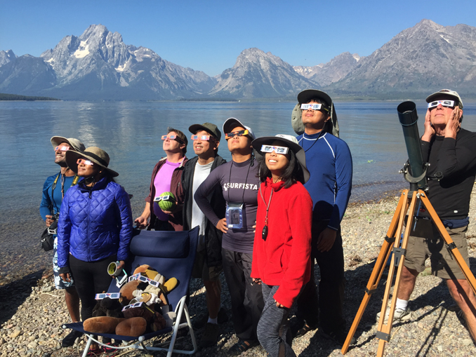 group in safety glassesswatching solar eclipse on an island in Jackson Lake, Wyoming