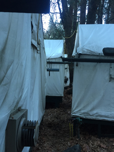 row of backside of tent cabins very near each other