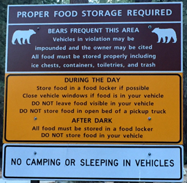 A sign that says: Proper food storage required. Bears frequent this area. Vehicles in violation may be impounded and the owner may be cited. All food must be stored properly including ice chests, containers, toiletries, and trash. DURING THE DAY. Store food in a food locker if possible. Close vehicle windows if food is in your vehicle. DO NOT leave food visible in your vehicle. DO NOT store food in open bed of a pickup truck. AFTER DARK. All food must be stored in a food locker. DO NOT store food in your vehicle. NO CAMPING OR SLEEPING IN VEHICLES