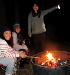 three women around a campfire