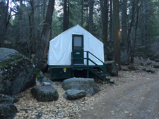 tent cabin surrounded by large rocks