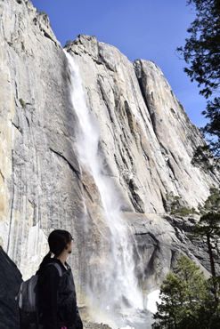 woman on trail turns to look at upper Yosemite falls