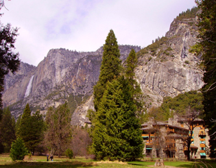 hotel with cliffs and waterfall in distance