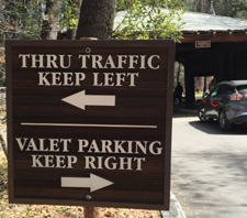 a sign that says thru traffic keep left valet parking keep right