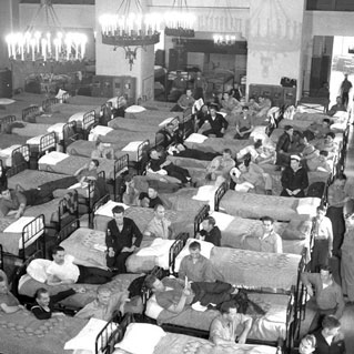 men in many beds with chandeliers above