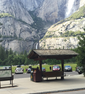 Yosemite Falls far in background, roofed bench area in foreground