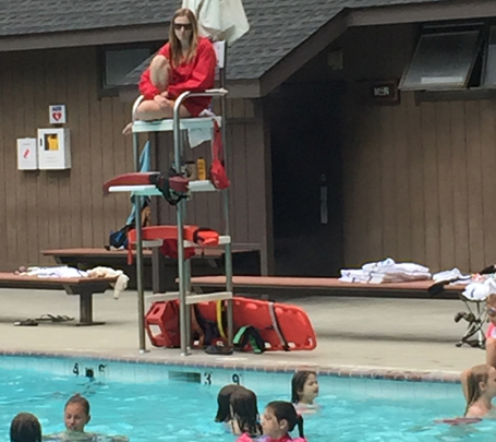 lifeguard sitting in lifeguard stand, rescue tubes below her on stand shelves