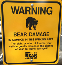 a sign that says: warning bear damage is common in this parking area