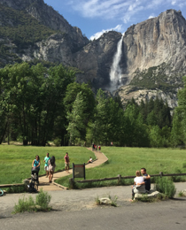 waterfall in background, people walking on wooden boardwalk in foreground