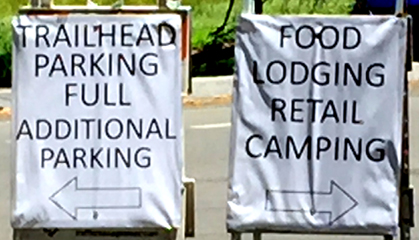 signs that say trailhead parking full and food lodging, retail