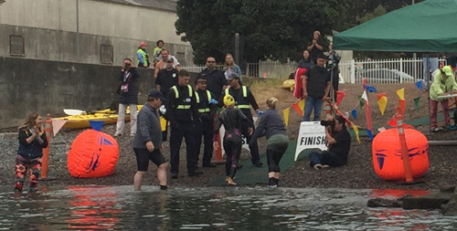 people helping a wetsuited swimmer