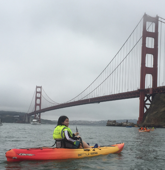 girl in kayak with Golden Gate bridge behind her