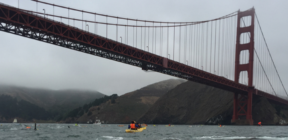 Golden Gate bridge with swimmers in the water below