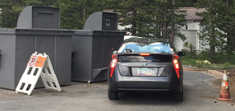two trash bins, no parking sign, car and red cone