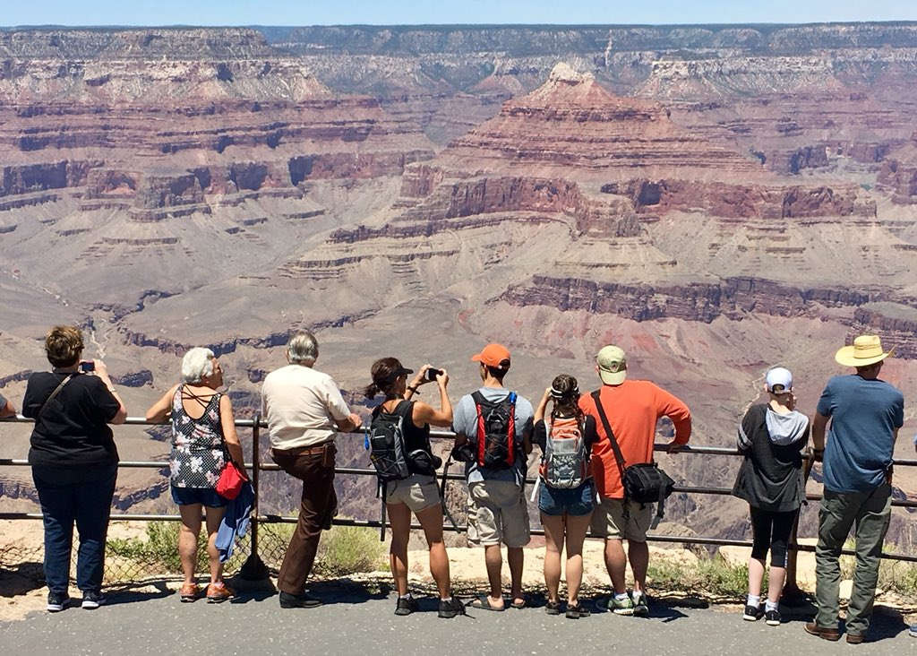 NPS photo of people leaning on a railing overlooking the Grand canyon