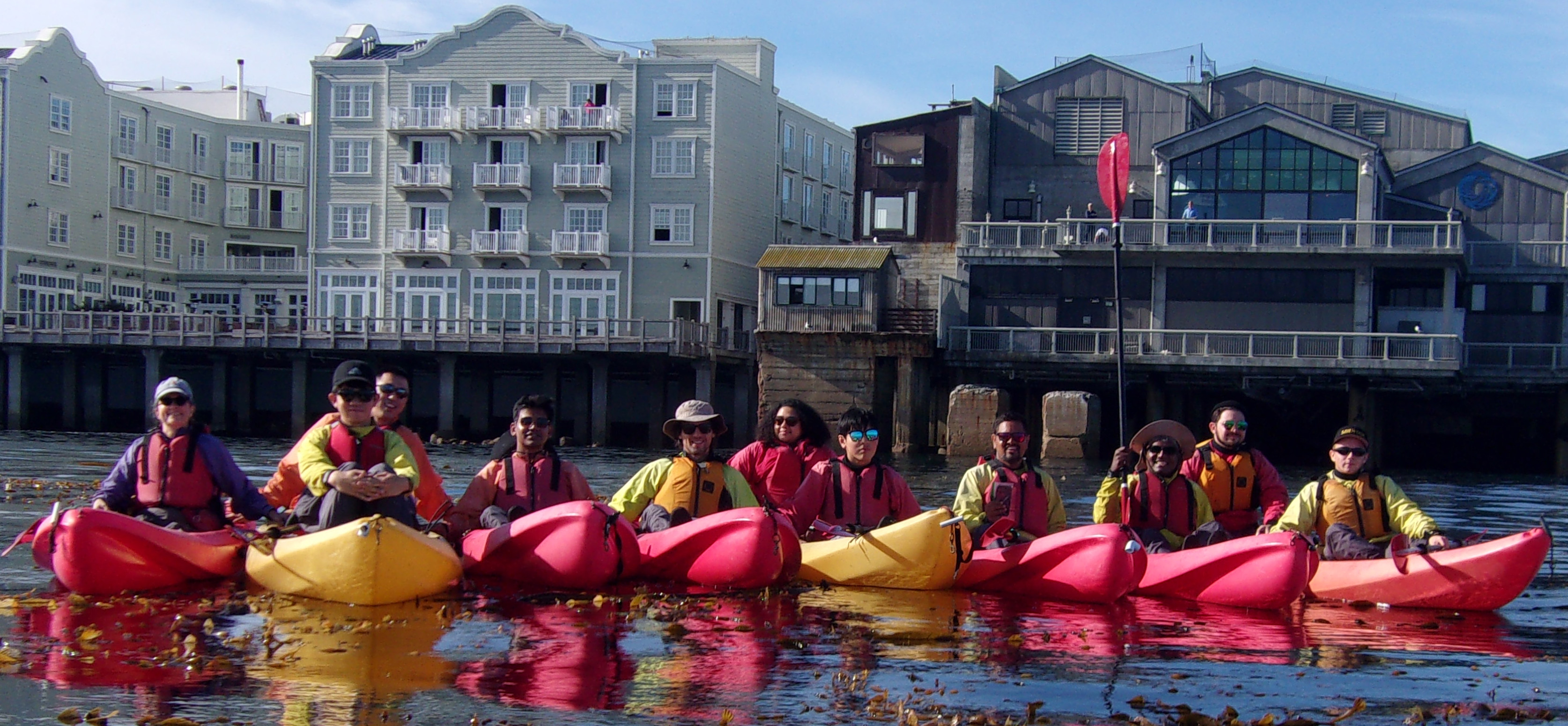 people in kayaks in a row front of the Monterey Bay Aquarium