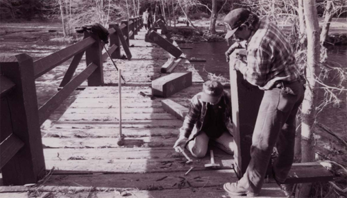 partially torn up wooden bridge with two men repairing it.
