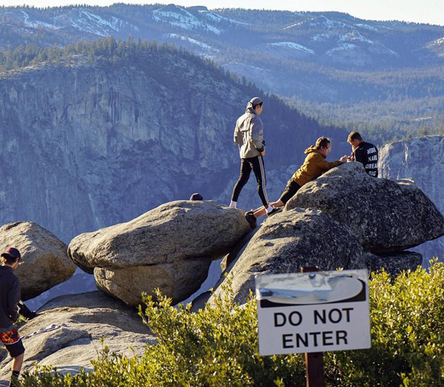 people climbing on rocks at the edge of a cliff just past a sign with large letters that says Do Not Enter