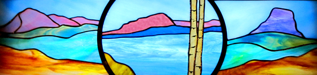 stained glass window showing mountains and lakes