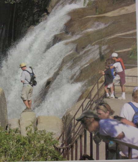 man on  the wrong side of a railing, with waterfall rushing very near him