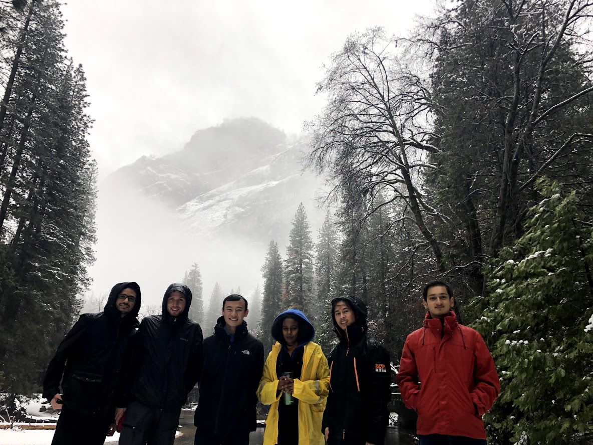 photo from Sean Pham of part of the group after brunch when we went to look at the paw prints, with cliffs behind cloaked in newly fallen snow, peeking out from behind clouds